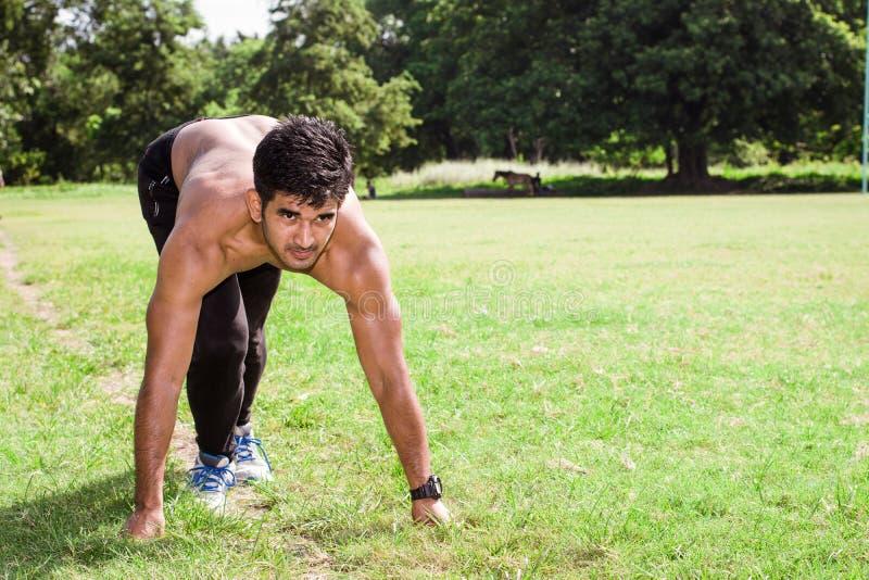 Atletische jonge mens die in de sportengrond lopen Gezond levensstijl, fitness en sportenconcept royalty-vrije stock fotografie
