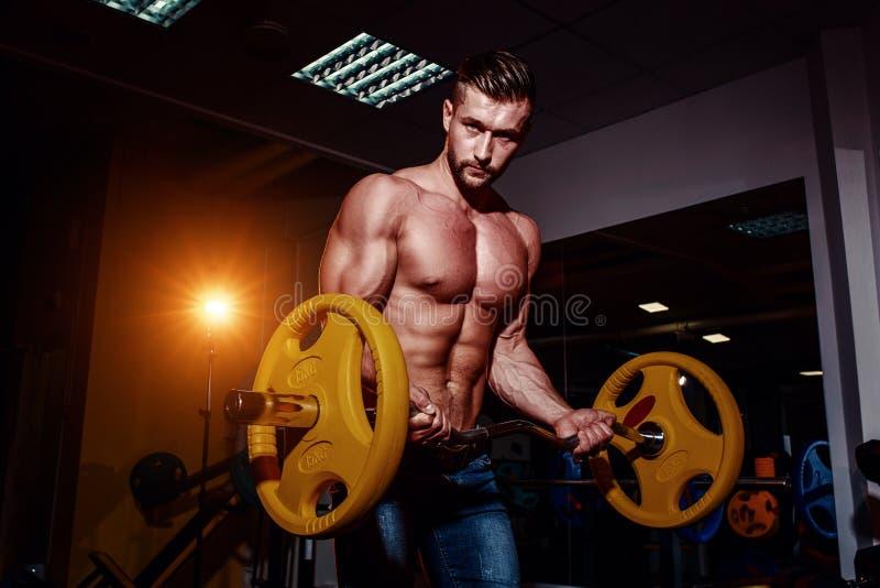 Atletische jonge mens die oefeningen met barbell in gymnastiek doen De knappe spierbodybuilderkerel werkt uit stock fotografie