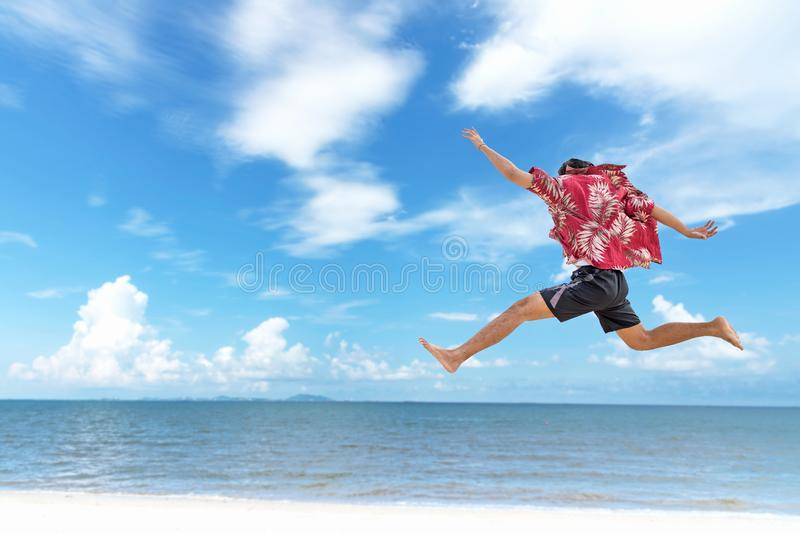 Atletische jonge mens die van de zomer genieten, die in een tropisch strand springen royalty-vrije stock foto