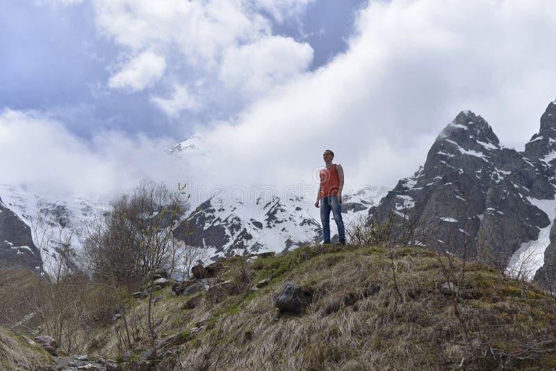Atletische jonge mens in het oranje overhemd bovenop sneeuw en de rotsachtige bergen royalty-vrije stock afbeeldingen