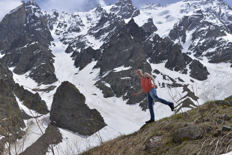 Atletische jonge mens in het oranje overhemd bovenop sneeuw en de rotsachtige bergen royalty-vrije stock afbeelding