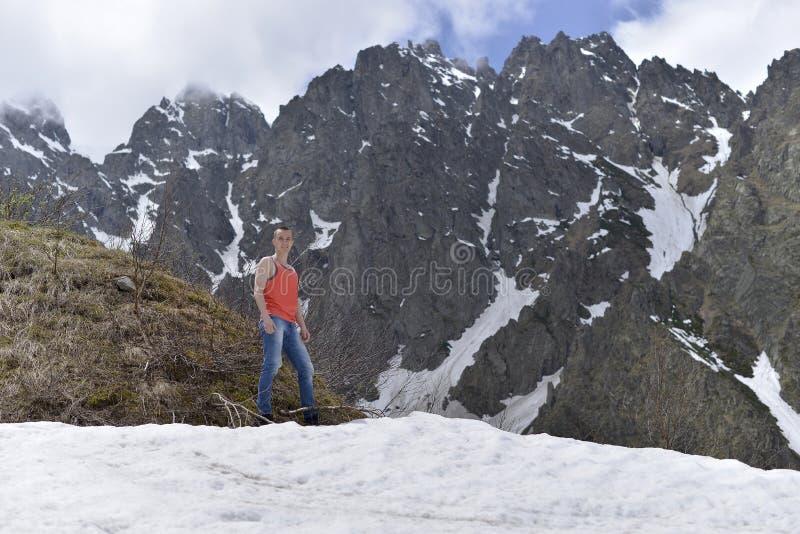 Atletische jonge mens in het oranje overhemd bovenop sneeuw en de rotsachtige bergen royalty-vrije stock foto's