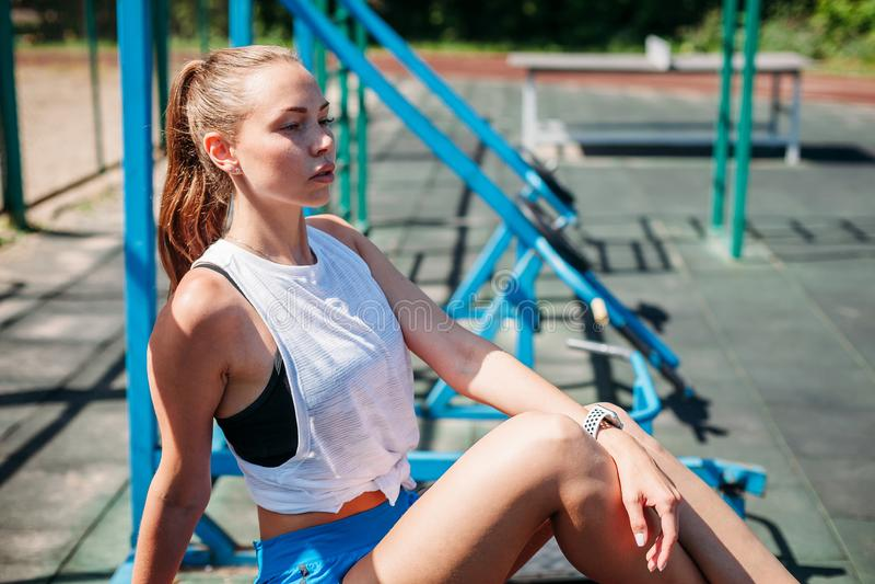 Atletische jonge mooie blondevrouw na sporten opleiding die op sportengrond rusten royalty-vrije stock afbeeldingen