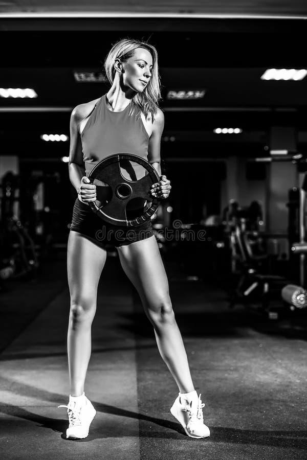 Atletische jonge sexy geschiktheidsvrouw op dieettrein en het uitoefenen in gymnastiek stock foto