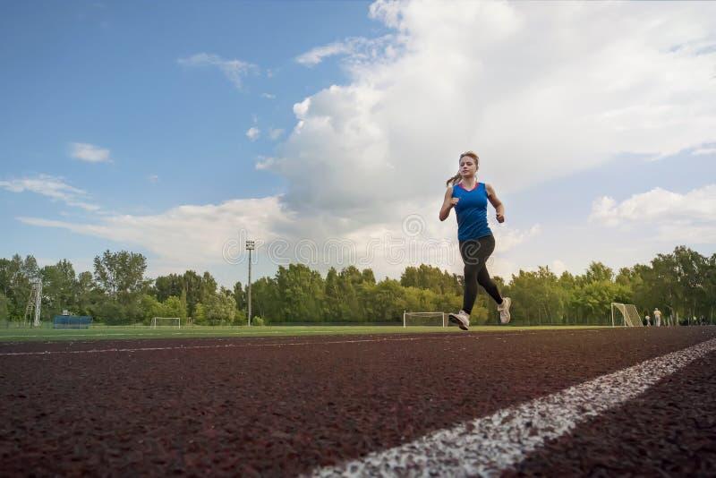 Atletische jonge sportvrouw die op renbaanstadion sprinten stock afbeeldingen