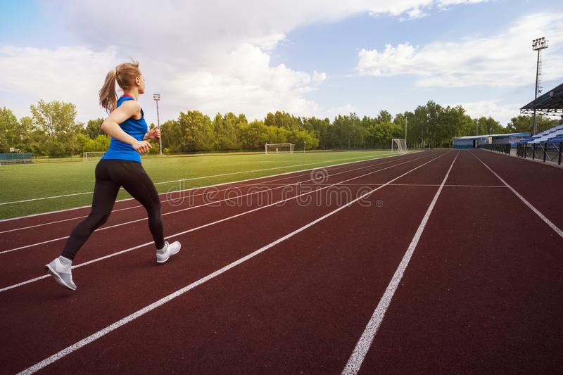 Atletische jonge sportvrouw die op renbaanstadion sprinten royalty-vrije stock foto