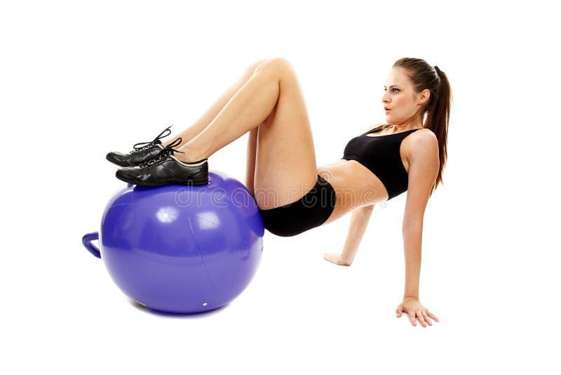 Atletische jonge vrouw die abs en benen met fitball uitwerken royalty-vrije stock foto