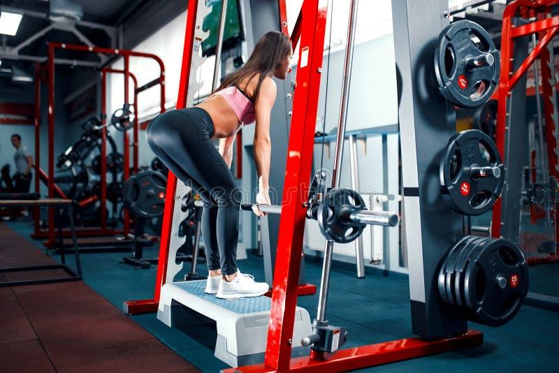 Atletische jonge vrouw die deadlift oefening in de machine van Smith doen stock afbeelding