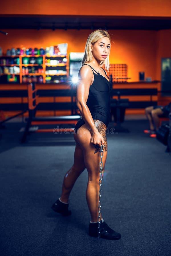 Atletische jonge vrouw die en geschiktheidstraining met gewichten in de gymnastiek stellen uitoefenen royalty-vrije stock afbeelding