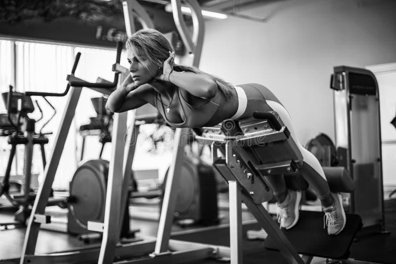 Atletische jonge vrouw die hyperextensie in de gymnastiek doen De achter en buikspieren van de vrouwenverbuiging stock fotografie