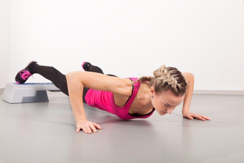 Atletische jonge vrouw die oefeningen doet stock afbeelding