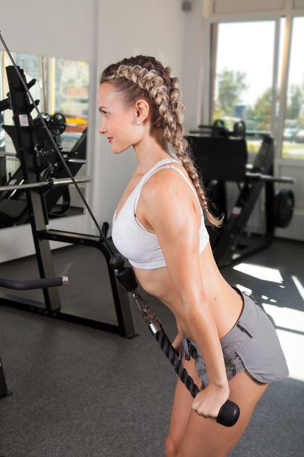 Atletische jonge vrouw opleiding op uitoefenaar stock afbeeldingen