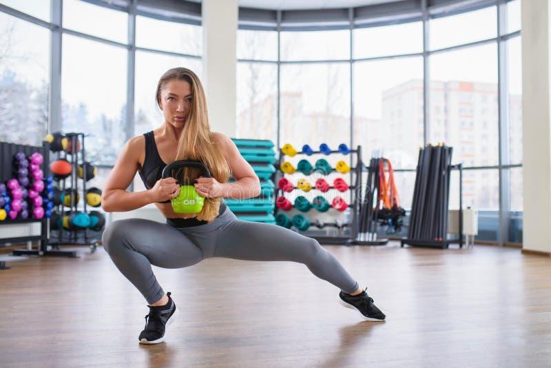 Atletische jonge vrouw tijdens training met kettlebell bij gymnastiek Mooi sexy meisje met het perfecte lichaam en vorm stellen royalty-vrije stock afbeeldingen