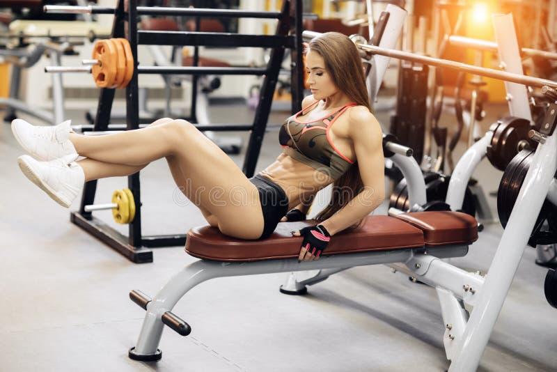 Atletische jonge vrouwenoefeningen voor abs op de bankpers stock foto's