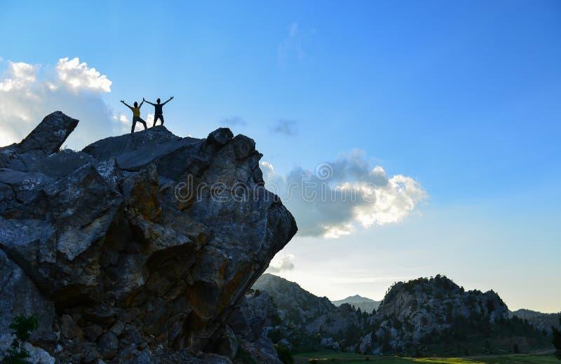 Atletische jongen en slank meisje die zich met opgeheven wapens op rotsachtige bergbovenkant bevinden die van de adembenemende me royalty-vrije stock foto