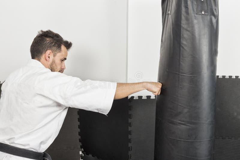 Atletische karatevechter die een krachtige voetschop geven aan zware B royalty-vrije stock foto