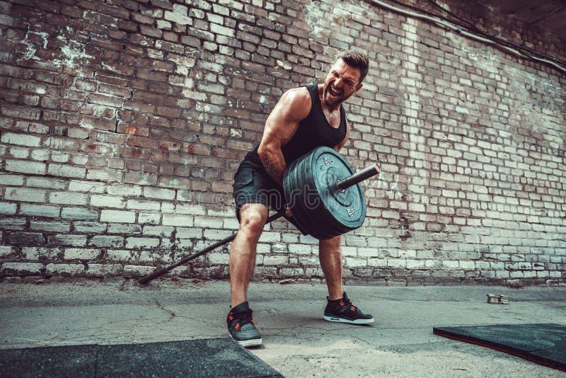 Atletische mens die met een barbell uitwerken Sterkte en motivatie Oefening voor de spieren van de rug stock afbeelding
