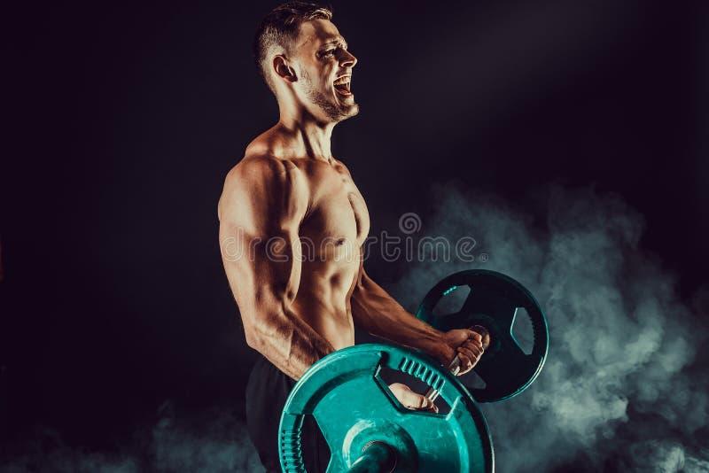 Atletische mens die oefeningen met domoren doen bij bicepsen Foto van sterk mannetje met naakt torso op donkere achtergrond stock fotografie
