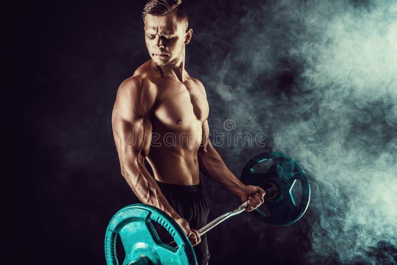 Atletische mens die oefeningen met domoren doen bij bicepsen Foto van sterk mannetje met naakt torso op donkere achtergrond stock foto's