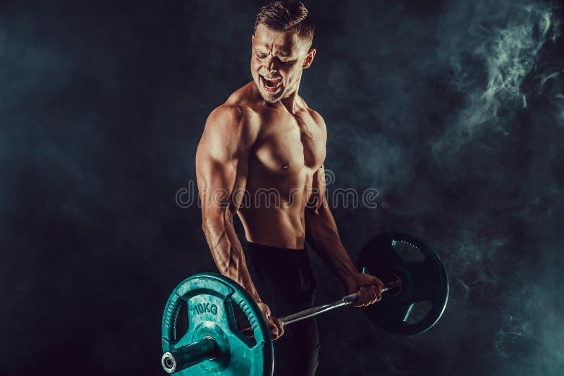 Atletische mens die oefeningen met domoren doen bij bicepsen Foto van sterk mannetje met naakt torso op donkere achtergrond royalty-vrije stock foto