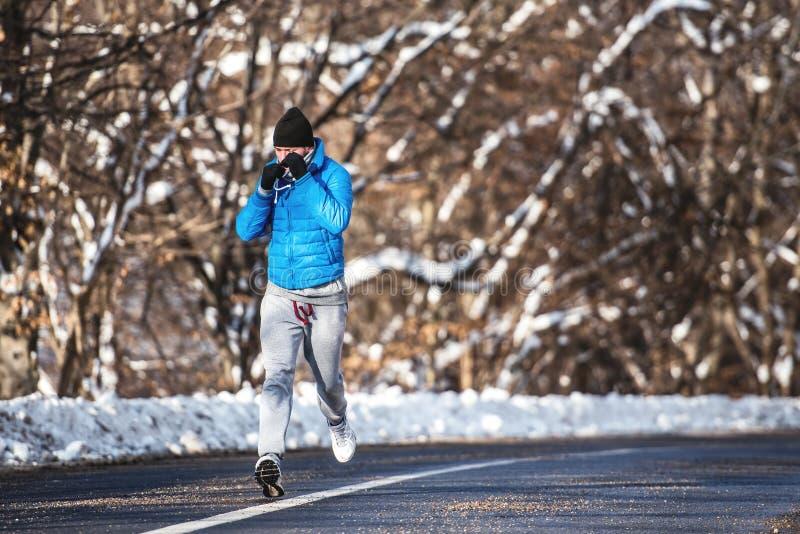 Atletische mens die op een bosweg en een opleiding lopen royalty-vrije stock foto's