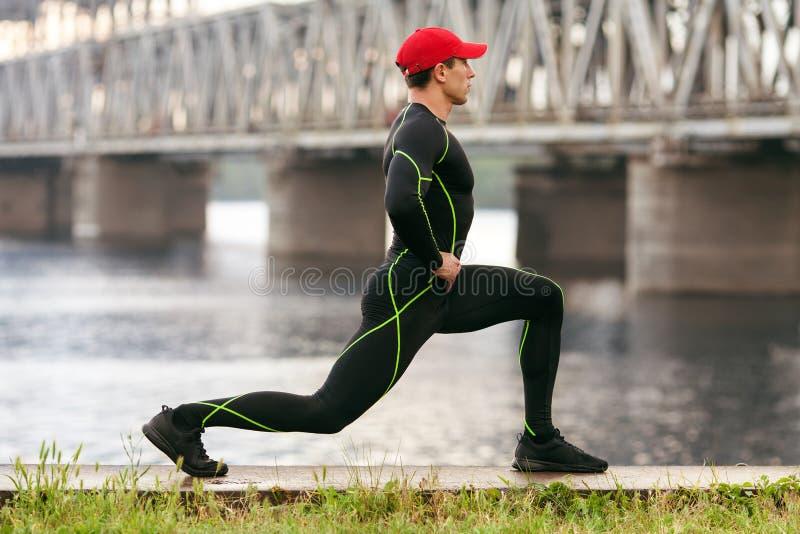Atletische mens die uitrekkende oefeningen doen, openlucht Actief mannetje die buitenkant op de achtergrond van de brug uitwerken royalty-vrije stock foto's