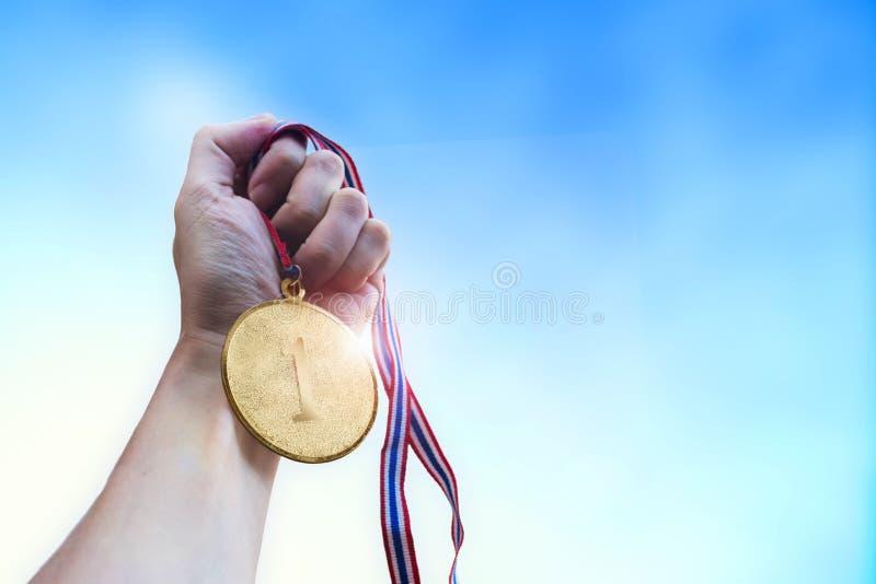 Atletische mensenhand die gouden muntstukmedaille houden stock fotografie