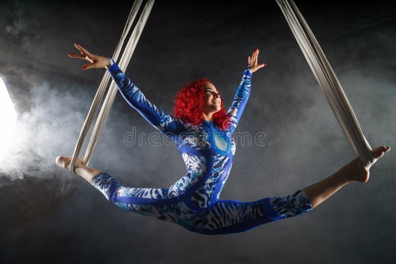 Atletische sexy luchtcircuskunstenaar met roodharige in blauw kostuum die in de lucht met saldo dansen stock foto's