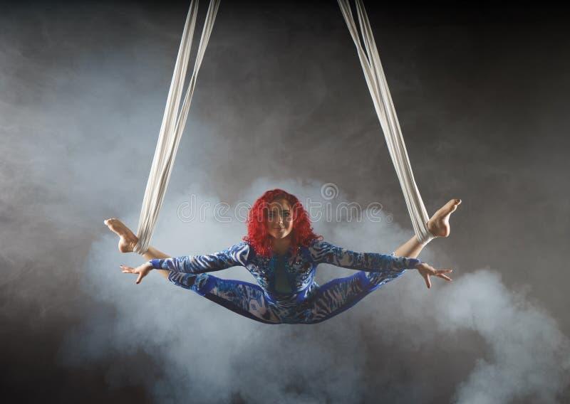 Atletische sexy luchtcircuskunstenaar met roodharige in blauw kostuum die in de lucht met saldo dansen stock fotografie