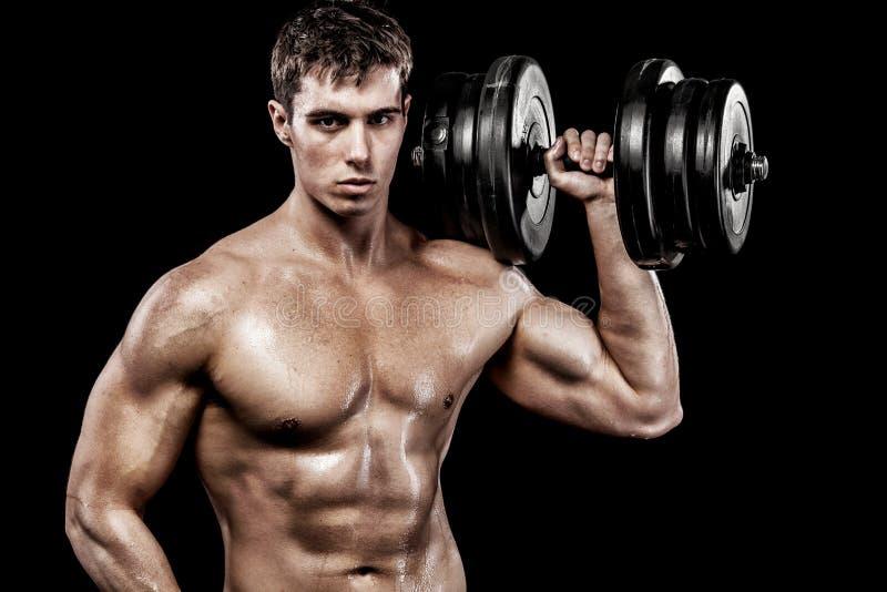 Atletische shirtless jonge sportenmens - het geschiktheidsmodel houdt de domoor in gymnastiek Exemplaar ruimtevoorst gedeelte uw  stock afbeeldingen