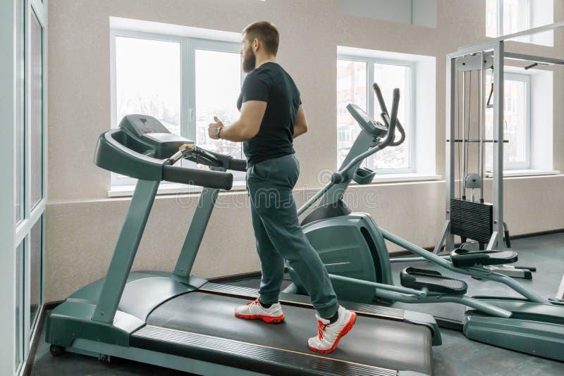 Atletische spier gebaarde mens die op tredmolens in moderne sportgymnastiek lopen Fitness, sport, opleiding, mensenconcept stock afbeelding