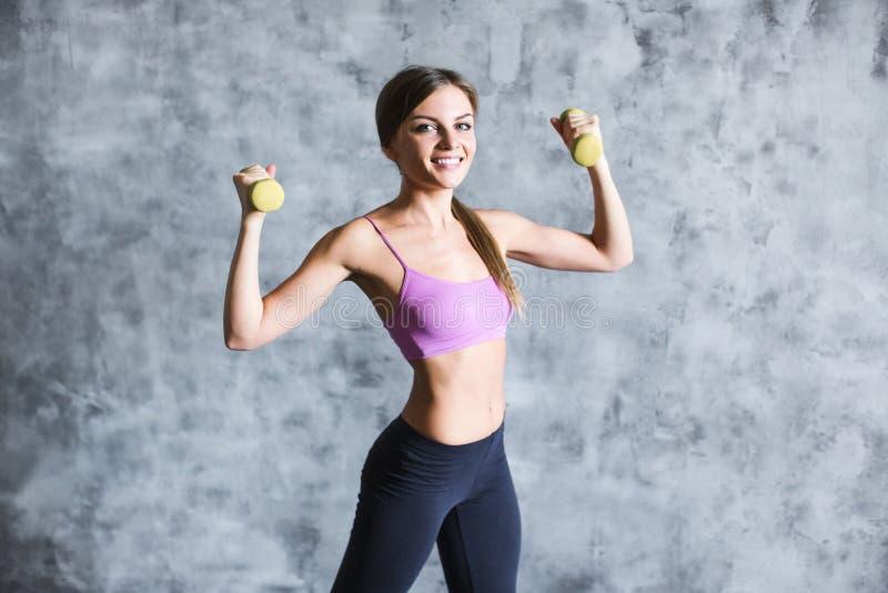 Atletische sportieve vrouw die met domoren op een grijze modieuze achtergrond opheffen royalty-vrije stock fotografie