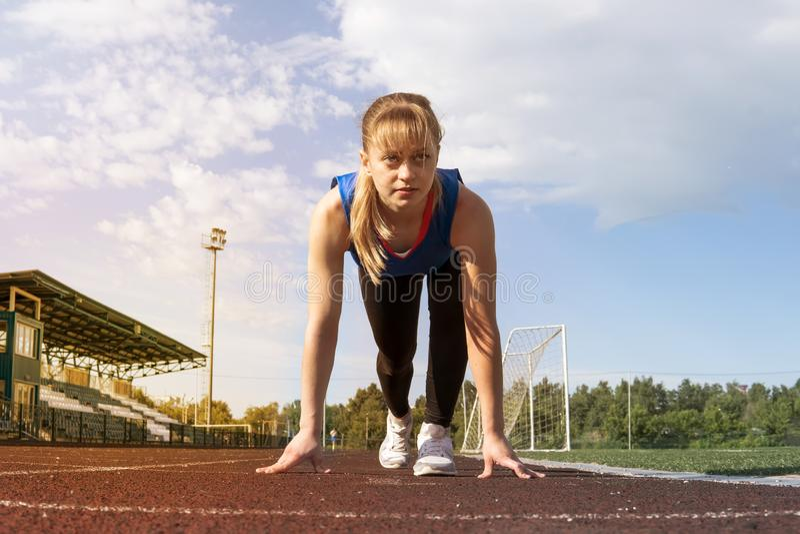 Atletische tiener in beginpositie inzake spoor Concept zich vooruit het bewegen stock fotografie