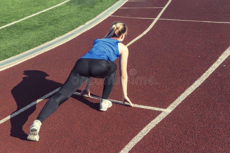 Atletische tiener in beginpositie inzake spoor Concept zich vooruit het bewegen royalty-vrije stock foto