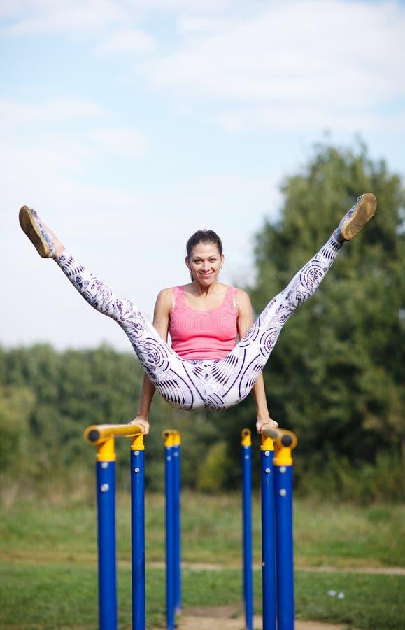 Atletische turner die op brug uitoefenen stock fotografie