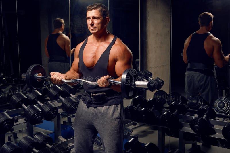 Atletische, volwassen mens die in de gymnastiek uitoefenen stock foto