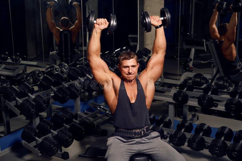 Atletische, volwassen mens die in de gymnastiek uitoefenen stock afbeeldingen