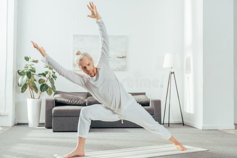 atletische volwassen mens het praktizeren yoga op mat royalty-vrije stock afbeelding