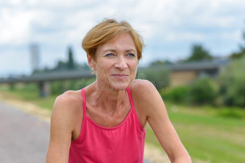 Atletische vrouw die aan rust na een training hurken stock afbeeldingen
