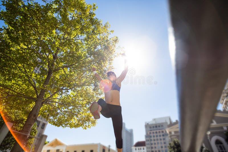 Atletische vrouw die en wapens in de lucht omhoog houden springen stock afbeelding