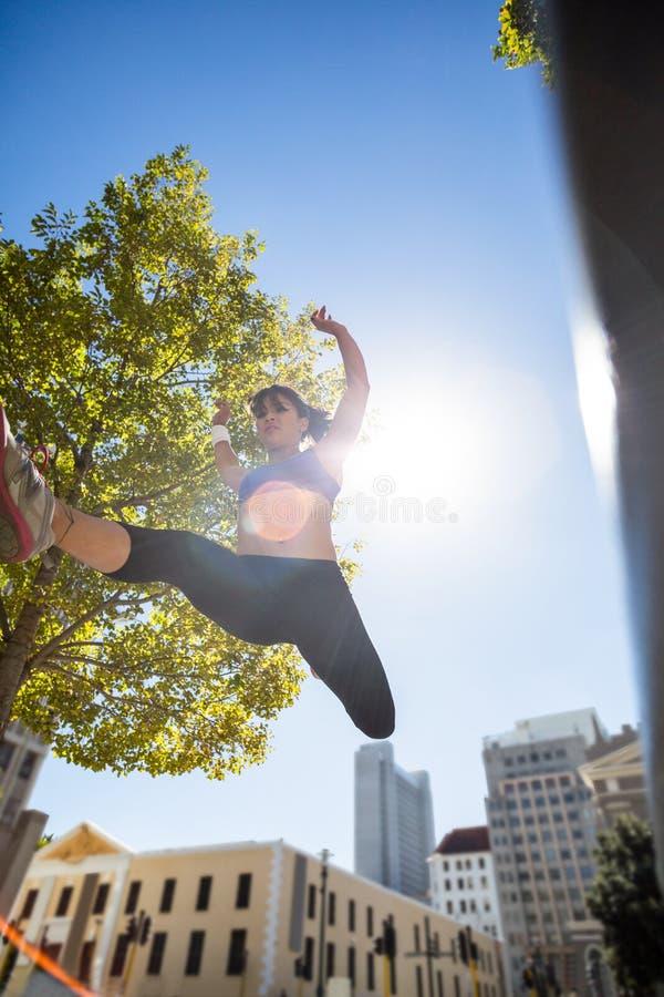 Atletische vrouw die en wapens in de lucht omhoog houden springen stock fotografie