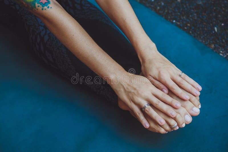 Atletische vrouw die haar benen in openlucht uitrekken stock fotografie