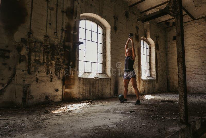 Atletische vrouw die kettlebell schommeling in een oud gebouw doen stock afbeeldingen