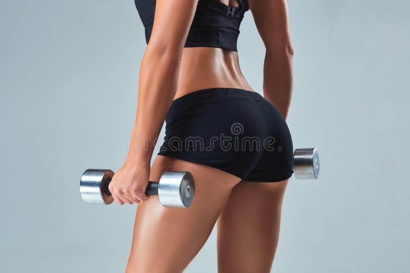 Atletische vrouw die omhoog spieren met domoren op grijze achtergrond pompen stock afbeeldingen