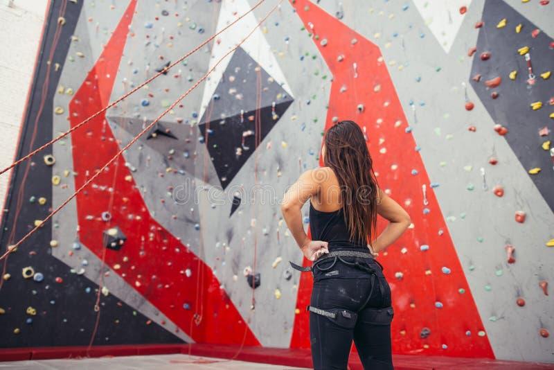 Atletische vrouw die voor kabel voorbereidingen treffen die oefening beklimmen bij de lokale gymnastiek B stock foto