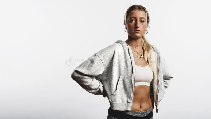 Atletische vrouw die zich in trainingkleren bevinden stock foto's