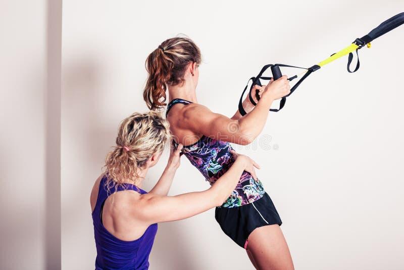 Atletische vrouw en persoonlijke trainer stock fotografie