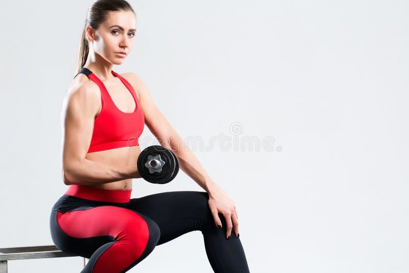 Atletische vrouw met domoren die die sportoefening doen, op grijze achtergrond wordt geïsoleerd stock foto