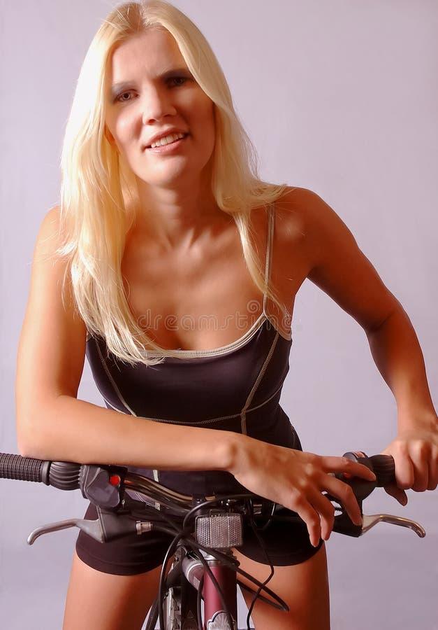Atletische vrouw op fiets royalty-vrije stock fotografie