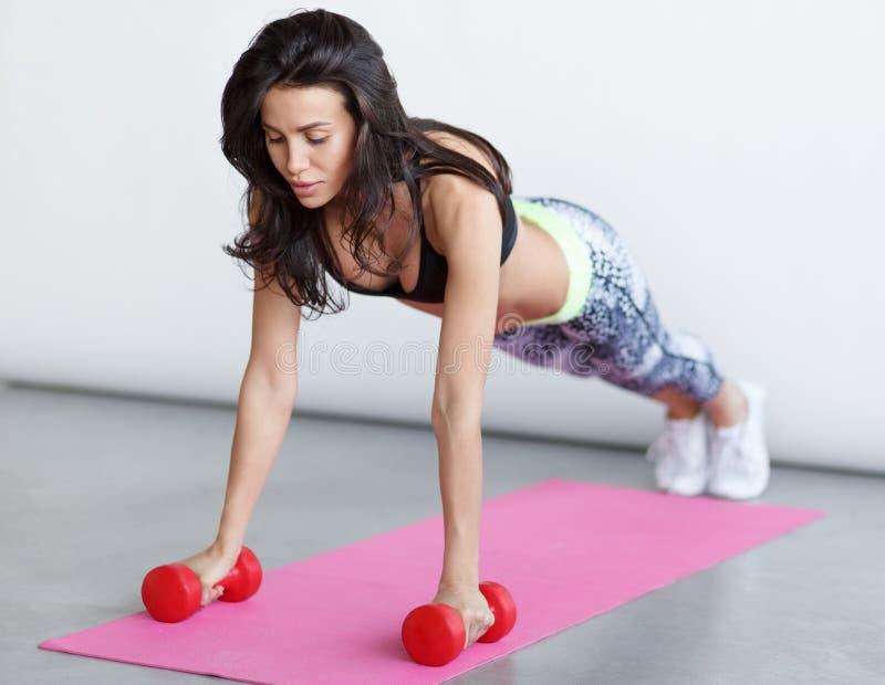Atletische vrouw opleiding op roze mat stock afbeeldingen